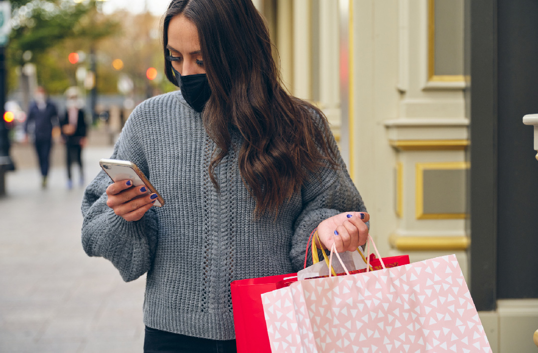 Lady with mask on looking at phone and carrying bags